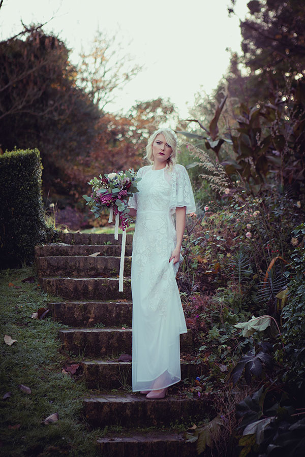 Botanical Vintage Northcourt Manor styled bridal photoshoot 2018. Holding a beautiful bouquet of flowers, the bride stands in the grounds of the manor house wearing a vintage white wedding dress sourced by Botanical Vintage. The manor house is behind her, and she stands upon the steps leading up to the higher gardens within the manor grounds.