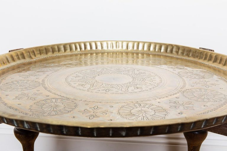 Vintage crockery and prop hire. This is a photograph of a large brass coloured Moroccan tray table. The tray is etched with a beautifully realised mandala. Sourced by Botanical Vintage.