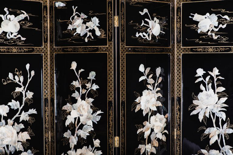 Vintage crockery and prop hire. This is a photograph of an oriental vintage dress screen. It is coloured black and gold and has a beautiful white motif of flowers upon each section. Sourced by Botanical Vintage.