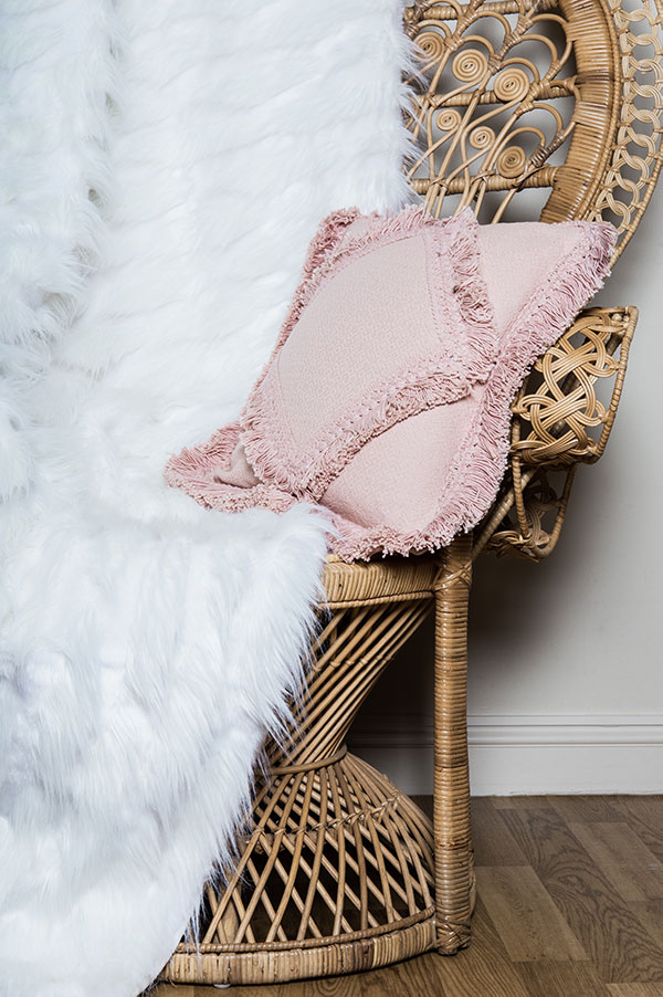 Vintage crockery and prop hire. This is a photograph of a single vintage peacock chair. There is a pink cushion in the seat and a faux fur white throw is draped upon the chair. Sourced by Botanical Vintage.