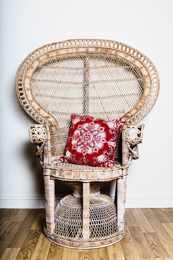 Vintage crockery and prop hire. This is a photograph of a single vintage peacock chair. There is a red cushion in the seat. Sourced by Botanical Vintage.