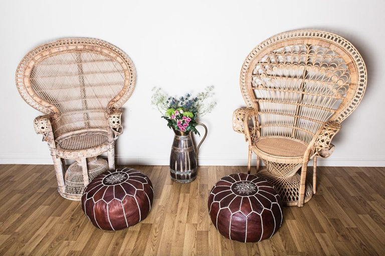 Vintage crockery and prop hire. This is a photograph of a two brown coloured vintage moroccan poufs sat in front of two vintage peacock chairs. It is lavishly segmented with white stitching and on top is an ornate mandala-style design. Sourced by Botanical Vintage.