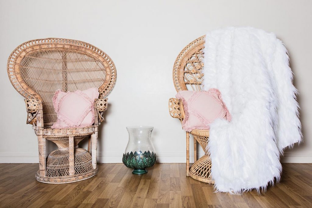 Vintage crockery and prop hire. This is a photograph of two vintage peacock chairs adorned with cushions. Between them is a vintage Lotus hurricane jar. sourced by Botanical Vintage.