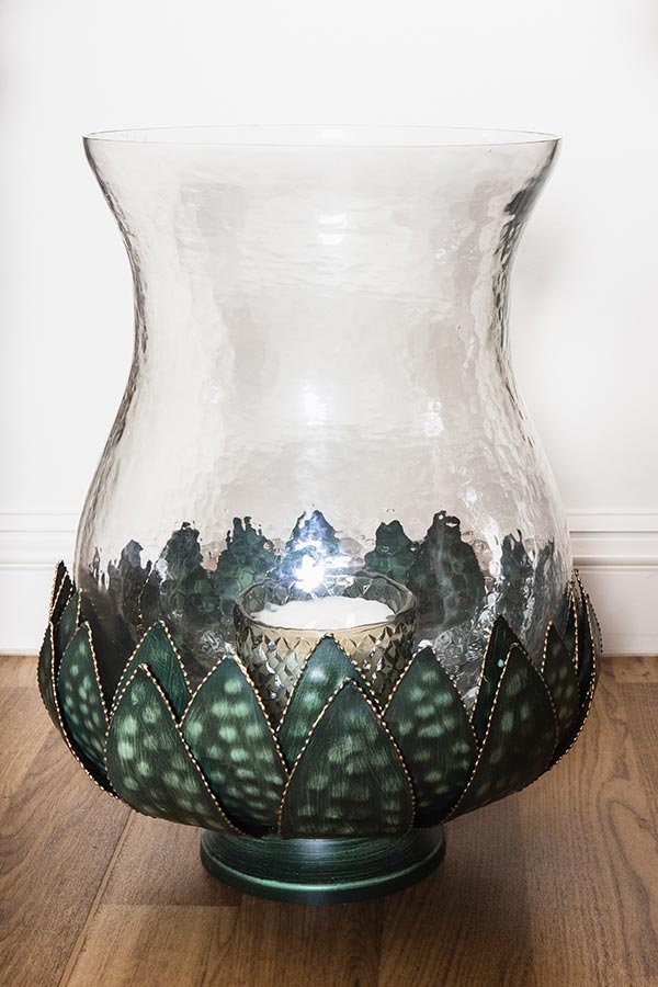 Vintage crockery and prop hire. This is a photograph of a dappled glass lotus hurricane jar. It is patterned with green leaf shapes at its base. sourced by Botanical Vintage.