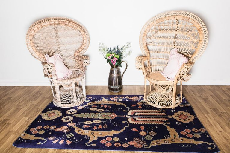 Vintage crockery and prop hire. This is a photograph of 2 vintage peacock chairs sitting atop a beautifully designed art deco rug. sourced by Botanical Vintage.