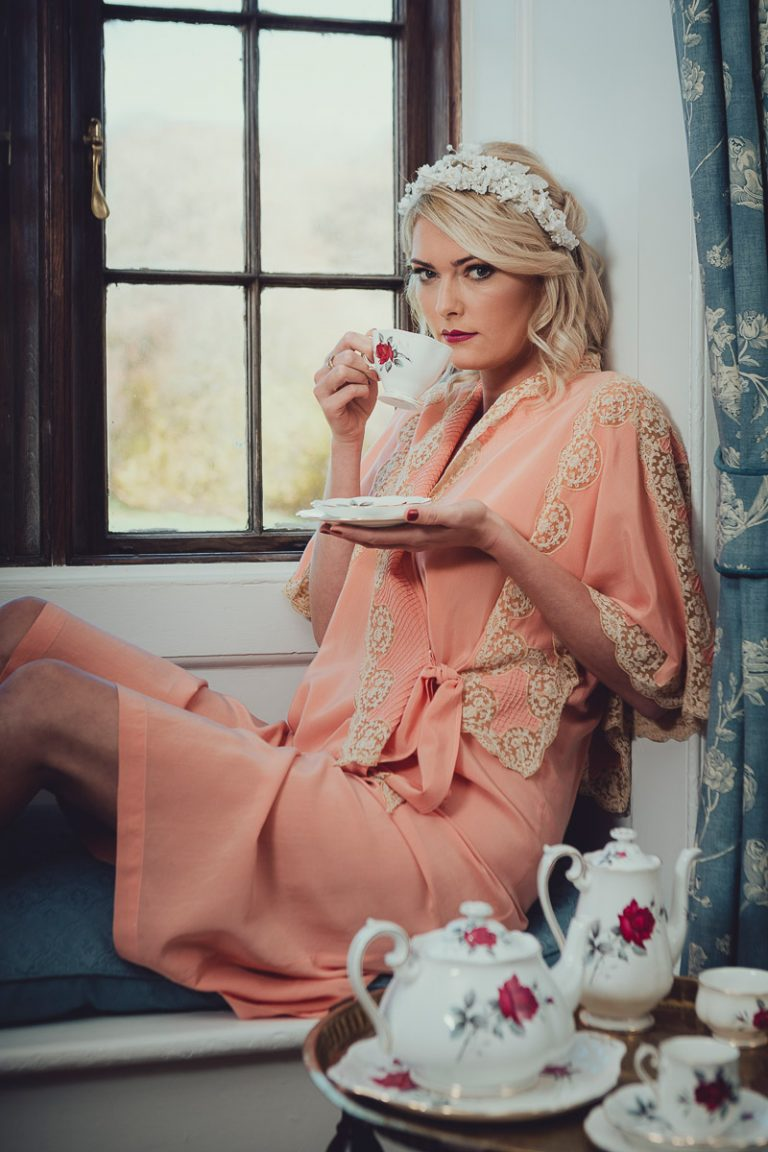 Botanical Vintage Northcourt Manor styled bridal photoshoot 2018. A photograph in the bedroom as the bride gets ready. The bride is wearing a peach coloured vintage dressing gown, looking out of the bedroom window and holding a dainty teacup.
