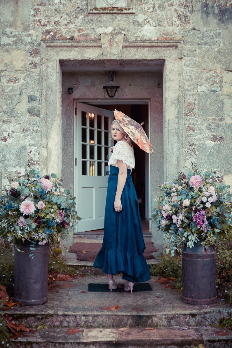 Botanical Vintage Northcourt Manor styled bridal photoshoot 2018. Holding an orange oriental-style parasol, the bride looks over a huge bouquet of flowers and is wearing a white and blue gypsy style vintage dress sourced by Botanical Vintage.