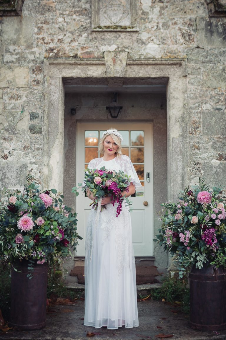 Botanical Vintage Northcourt Manor styled bridal photoshoot 2018. Holding a beautiful bouquet of flowers, the bride stands at the main entrance of the manor house wearing a vintage white wedding dress sourced by Botanical Vintage. Two arrangements of flowers are either side of the bride. The flowers match her bouquet.