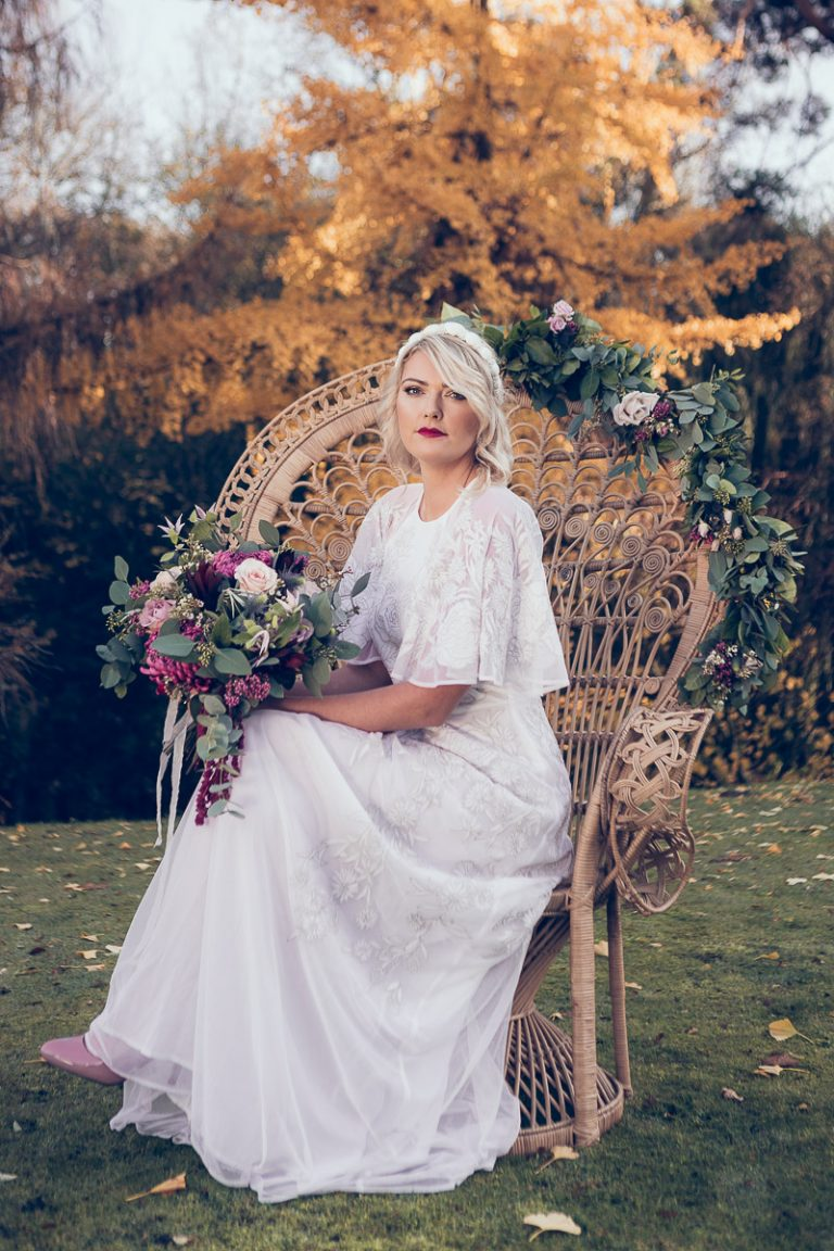 Botanical Vintage Northcourt Manor styled bridal photoshoot 2018. Holding a beautiful bouquet of flowers, the bride stands in the grounds of the manor house wearing a vintage white wedding dress sourced by Botanical Vintage. The bride sits upon a stunning bridal peacock chair in the garden. The atmosphere is bohemian.