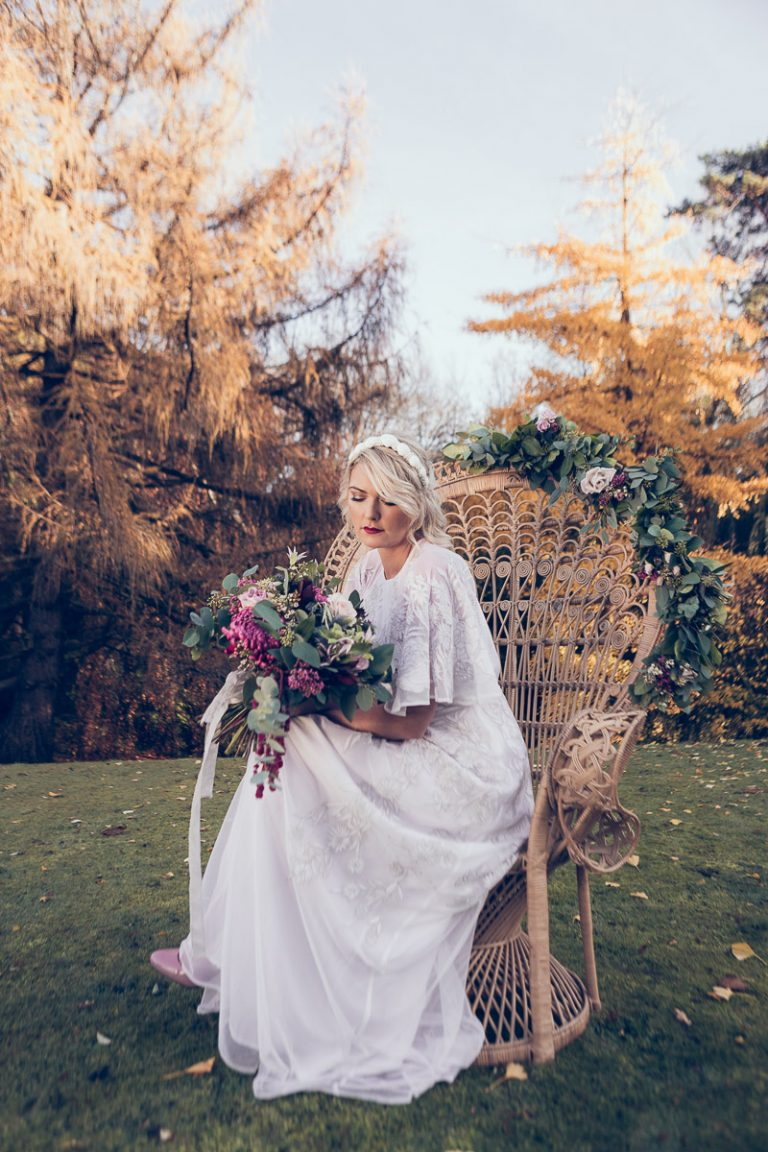 White wedding dress. Holding a beautiful bouquet of flowers, the bride stands in the grounds of the manor house wearing a vintage white wedding dress sourced by Botanical Vintage. The bride sits upon a stunning bridal peacock chair in the garden. The atmosphere is bohemian.