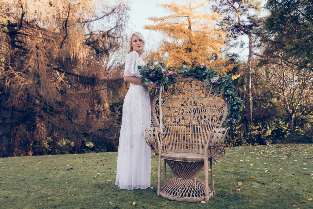 Bohemian bride is holding a beautiful bouquet of flowers, the bride stands in the grounds of the manor house wearing a vintage white wedding dress sourced by Botanical Vintage. The bride stands next to a stunning peacock chair in the garden. The atmosphere is bohemian.