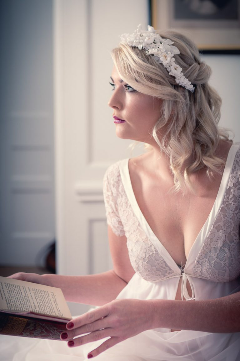 Botanical Vintage Northcourt Manor styled bridal photoshoot 2018. A photograph in the bedroom as the bride gets ready. The bride sits upon the bed, reading a book. The bride wears a white floral head-dress.