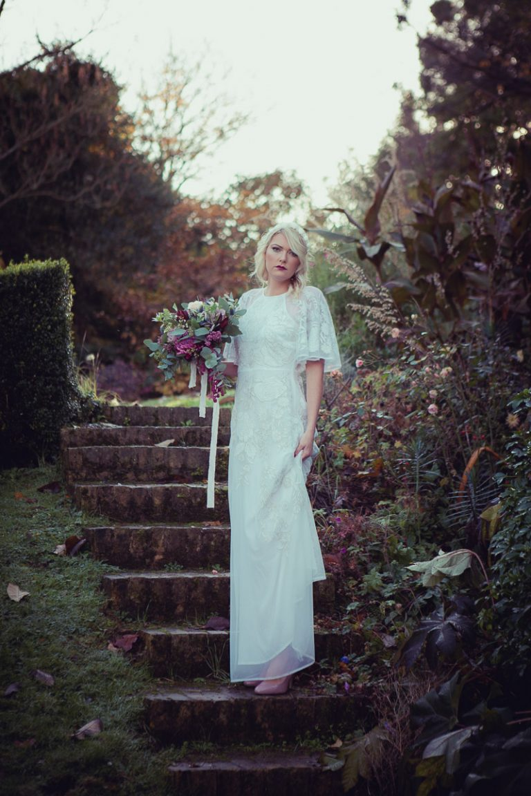 Standing upon steps the bride is holding a beautiful bouquet of flowers, the bride stands in the grounds of the manor house wearing a vintage white wedding dress sourced by Botanical Vintage. The manor house is behind her, and she stands upon the steps leading up to the higher gardens within the manor grounds.