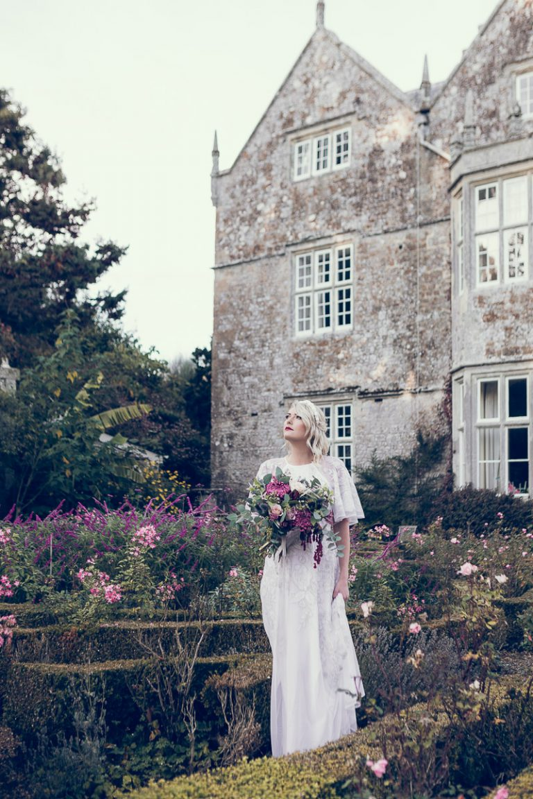 Whimsically looking skywards, our bride is holding a beautiful bouquet of flowers, the bride stands in the grounds of the manor house wearing a vintage white wedding dress sourced by Botanical Vintage. The manor house is behind her, and she stands in amongst the flowers of a Victorian style country garden.