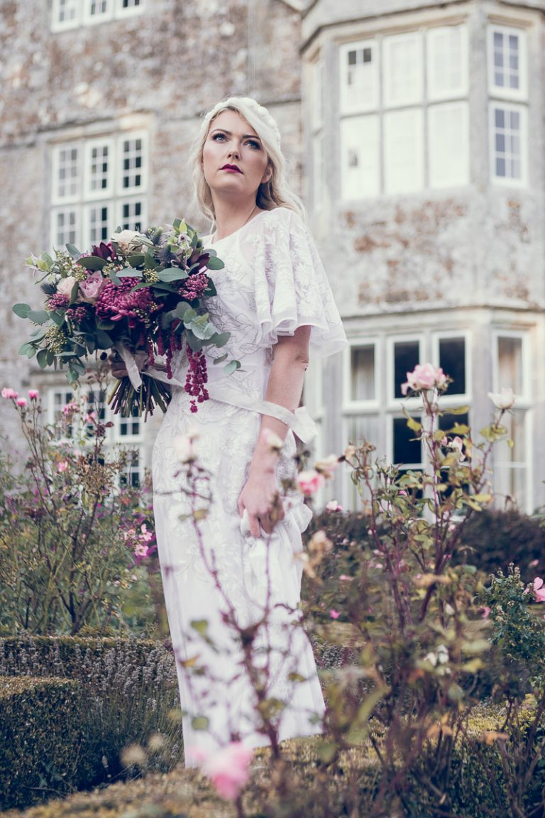Bohemian bride holding a beautiful bouquet of flowers, the bride stands in the grounds of the manor house wearing a vintage white wedding dress sourced by Botanical Vintage. The manor house is behind her, and she stands in amongst the flowers of a Victorian style country garden.