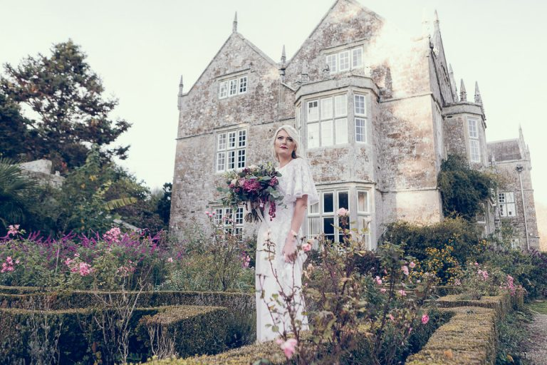 Sun streaked manor house as a backdrop to the english manor garden. Holding a beautiful bouquet of flowers, the bride stands in the grounds of the manor house wearing a vintage white wedding dress sourced by Botanical Vintage. The manor house is behind her, and she stands in amongst the flowers of a Victorian style country garden.