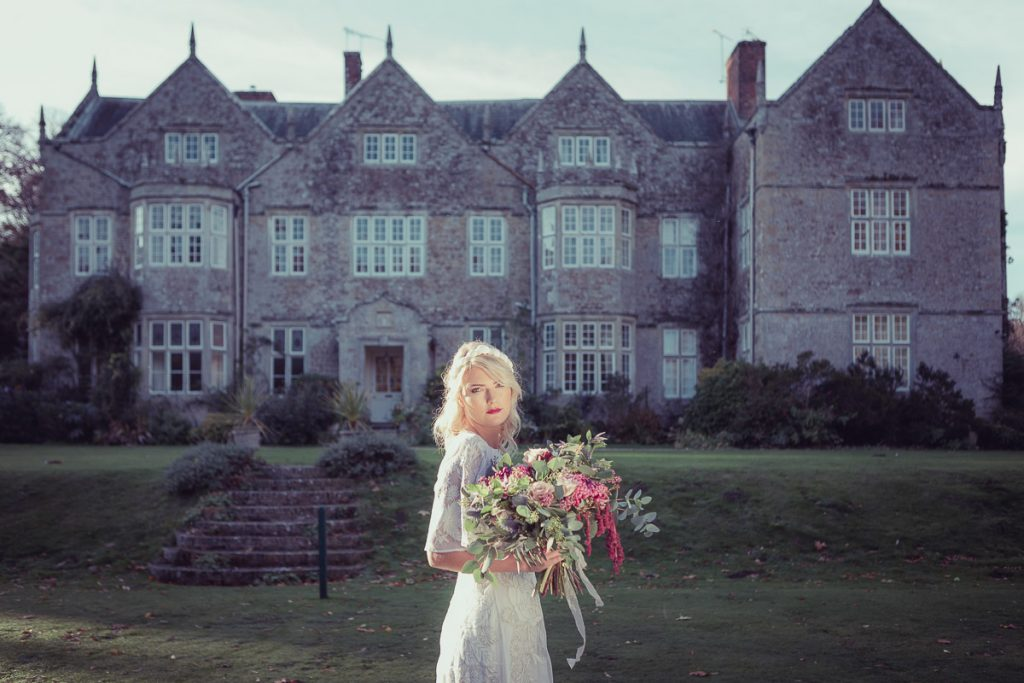 Sultry bride holding a beautiful bouquet of flowers, the bride stands in the grounds of the manor house wearing a vintage white wedding dress sourced by Botanical Vintage.