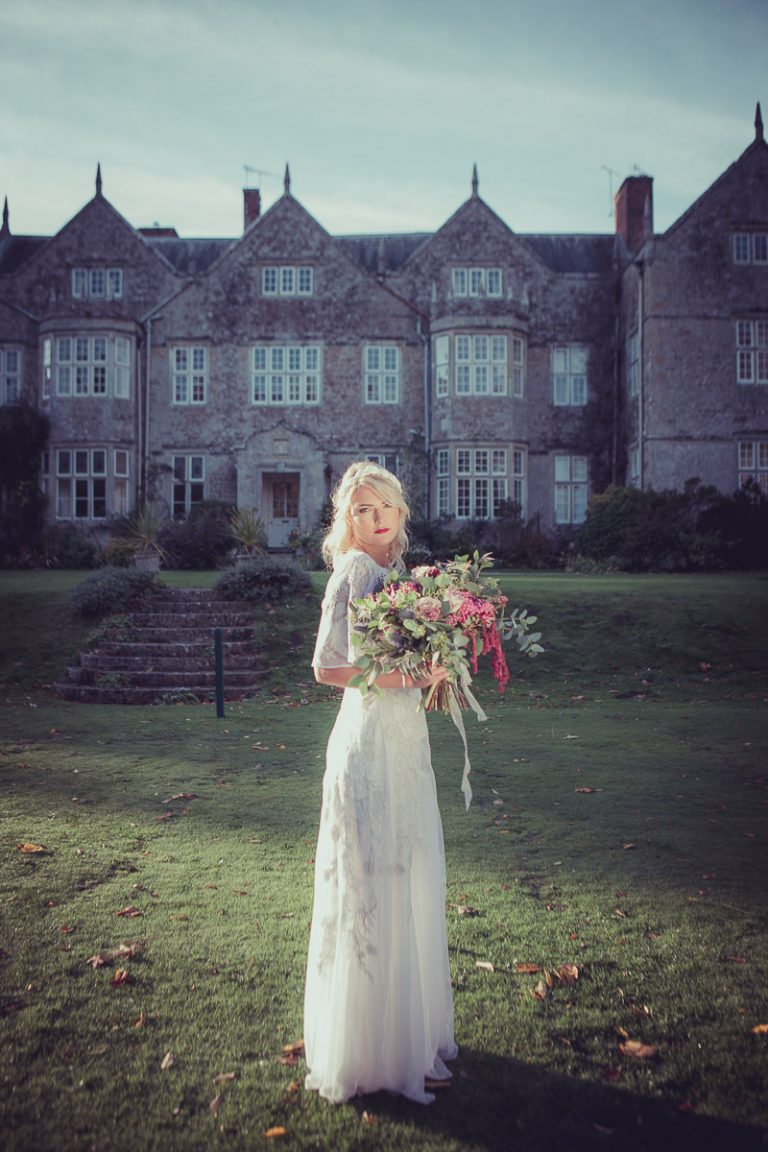 With the manor house as a backdrop, the bride is holding a beautiful bouquet of flowers, the bride stands in the grounds of the manor house wearing a vintage white wedding dress sourced by Botanical Vintage.