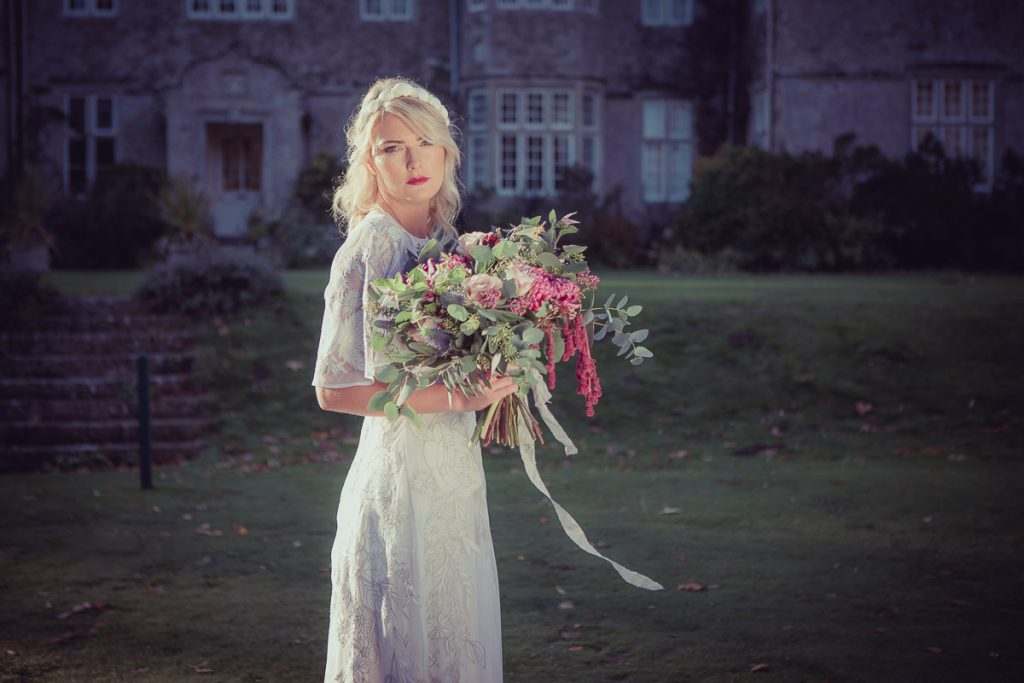Clasping a beautiful bouquet of flowers, the bride stands in the grounds of the manor house wearing a vintage white wedding dress sources by Botanical Vintage.