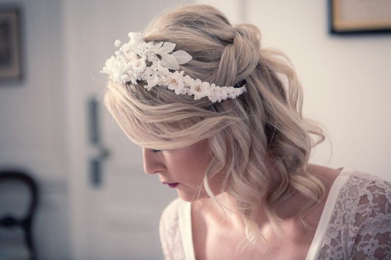 Botanical Vintage Northcourt Manor styled bridal photoshoot 2018. A photograph in the bedroom as the bride gets ready. The bride sits upon the bed, reading a book. The focus of this shot is on the white floral head-dress.