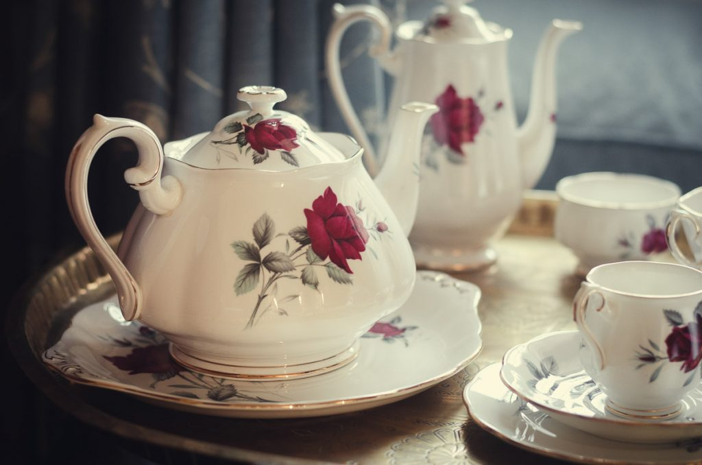 Botanical Vintage Northcourt Manor styled bridal photoshoot 2018. A photograph within the bedroom as the bride gets ready. The focus is a vintage tea-set including teacups, teapots and saucers. All have a matching rose pattern.