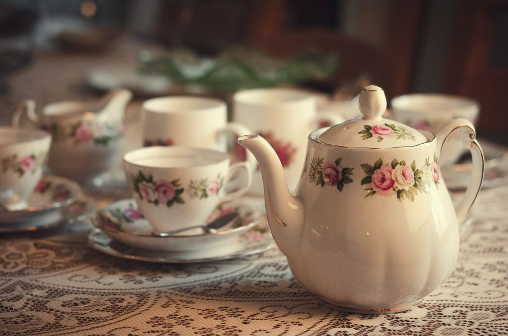 Botanical Vintage Northcourt Manor styled bridal photoshoot 2018. A photograph of the breakfast table. The focus is on a vintage teapot adorned with a rose pattern. The rest of the table is adorned with various vintage crockery including plates and cups.