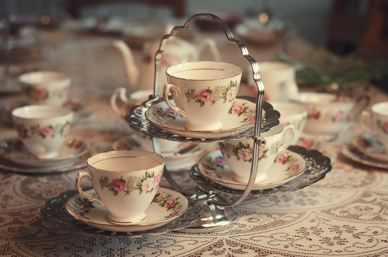 Botanical Vintage Northcourt Manor styled bridal photoshoot 2018. A photograph of the breakfast table. The focus is on three teacups on a vintage carrier. The rest of the table is adorned with various vintage crockery including plates and cups.