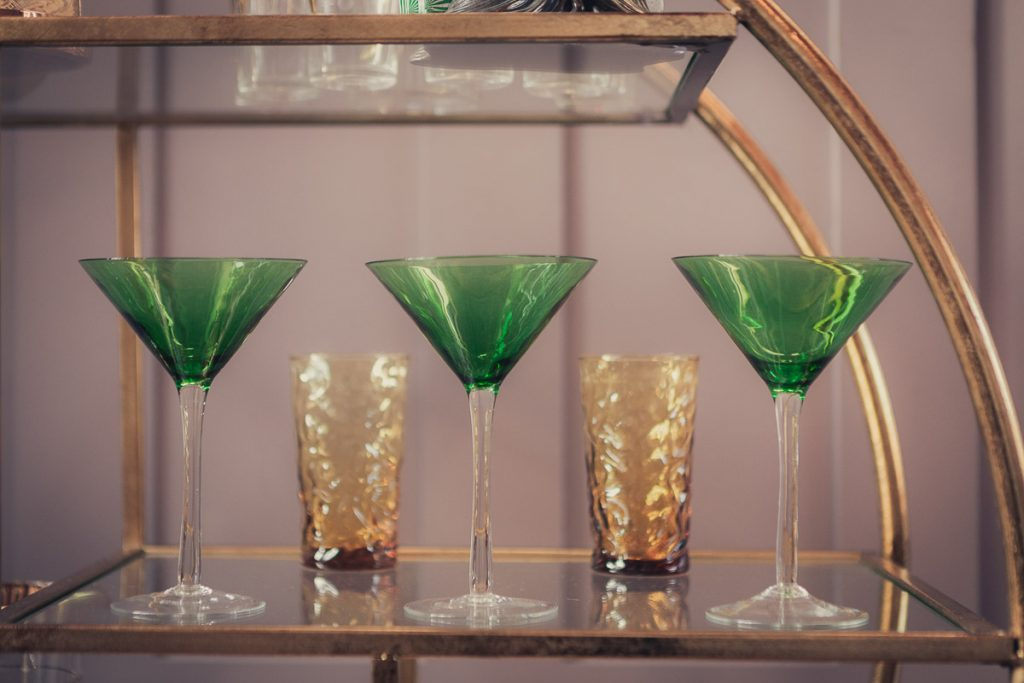 Botanical Vintage Northcourt Manor styled bridal photoshoot 2018. Three emerald green coloured vintage cocktail glasses sitting upon a round, gold coloured Art Deco drinks server. There are a selection of vintage glasses upon the server.