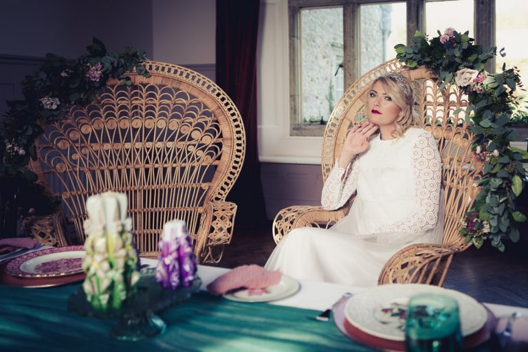 Botanical Vintage Northcourt Manor styled bridal photoshoot 2018. The bride reclines in a classical peacock chair at the dining table. The bride is wearing a glamorous head-dress and a classical cream coloured wedding dress sourced by Botanical Vintage. Autumnal light is streaming into the room behind her.