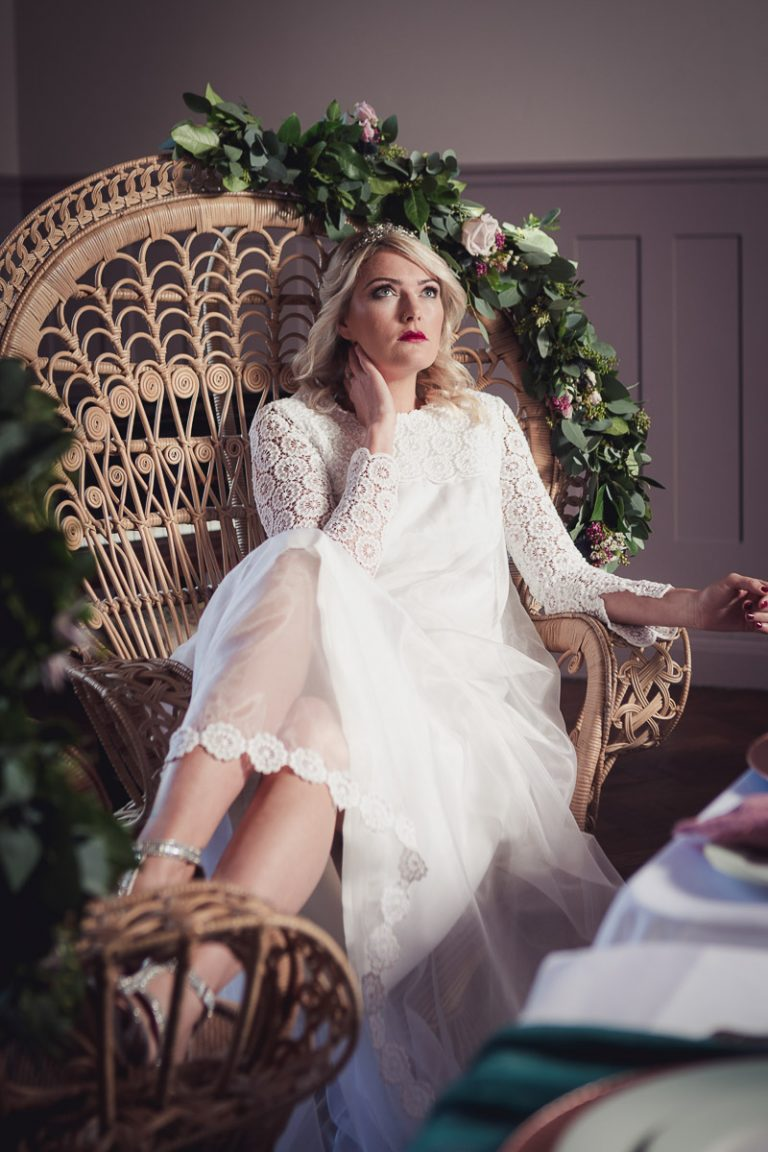 Botanical Vintage Northcourt Manor styled bridal photoshoot 2018. The bride reclines in a classical peacock chair at the dining table. The bride is wearing a glamorous head-dress and a classical cream coloured wedding dress sourced by Botanical Vintage.