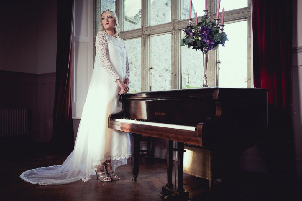 Botanical Vintage Northcourt Manor styled bridal photoshoot 2018. The bride stands beside a grand piano at the main window of the dining room. Upon the piano is a vintage candelabra adorned with flowers. The bride is wearing a glamorous head-dress and a classical cream coloured wedding dress sourced by Botanical Vintage.