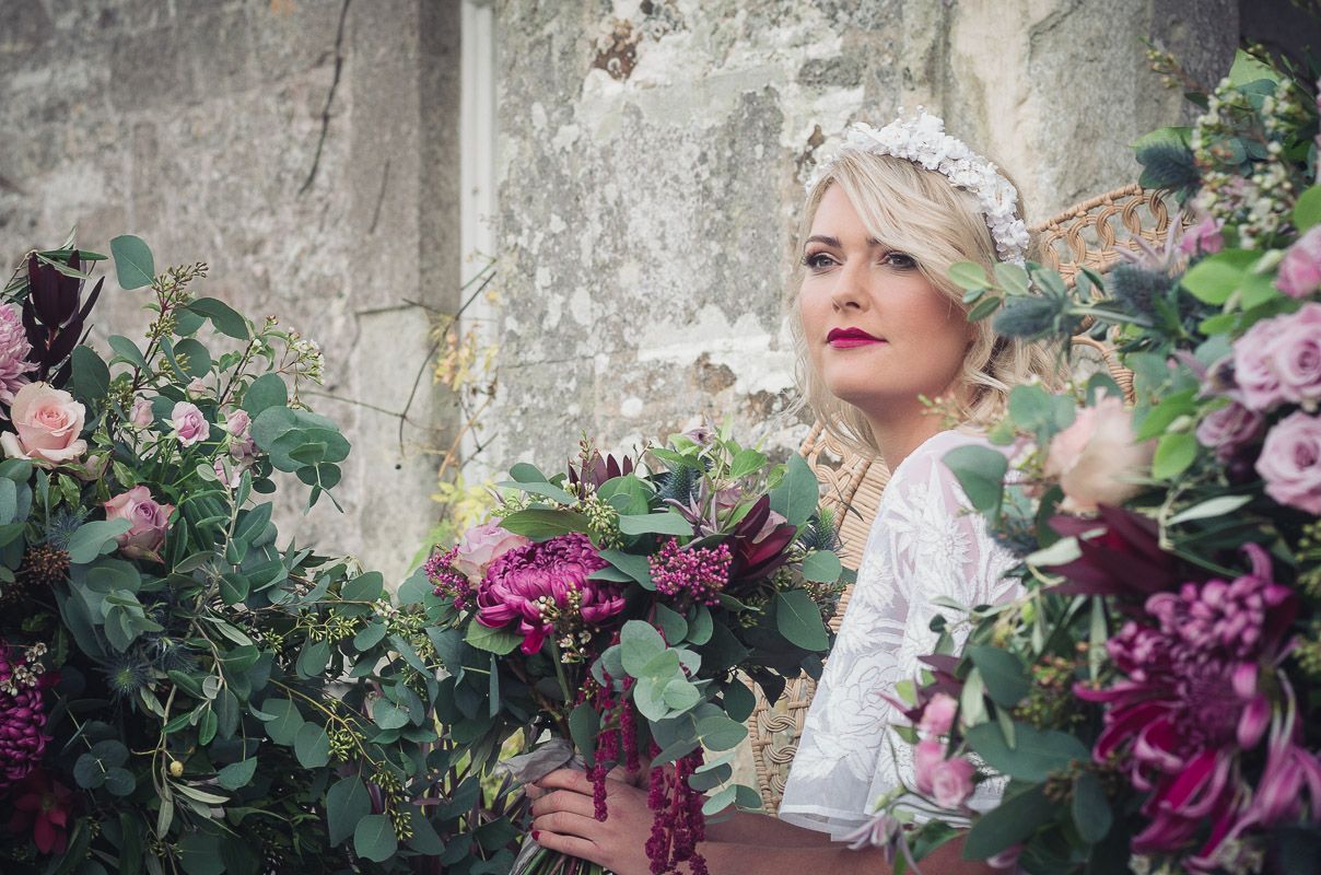 Botanical Vintage Northcourt Manor styled bridal photoshoot 2018. Holding a beautiful bouquet of flowers, the bride sits in a classical peacock chair at the main entrance of the manor house. She wears a vintage white wedding dress sourced by Botanical Vintage. Two arrangements of flowers are either side of the bride. The flowers match her bouquet.