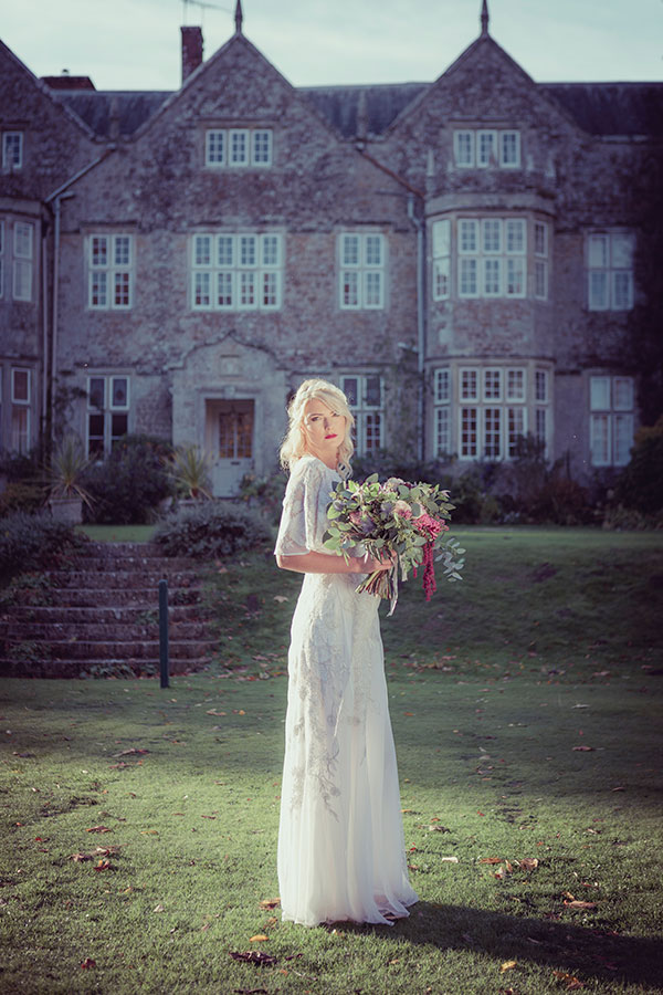 Holding a beautiful bouquet of flowers, the bride stands in the grounds of the manor house wearing a vintage white wedding dress sourced by Botanical Vintage.