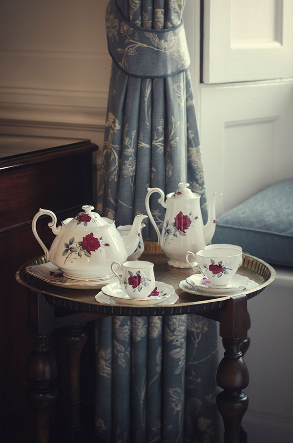 A photograph within the bedroom as the bride gets ready. The focus is a vintage tea-set including teacups, teapots and saucers. All have a matching rose pattern.