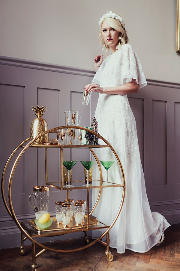 A photograph of the bride in a vintage white wedding dress and head-dress holding a green cocktail glass from an Art Deco drinks server. In the background, a styled dining room is laden with vintage crockery and candelabras, all sourced by Botanical Vintage.