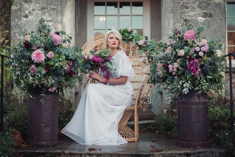 Bohemian Bride surrounded by flowers. She sits upon a peacock chair and holds a bouquet.