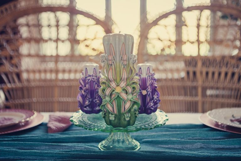 A photograph of an ornate candle in a holder sat at the foot of the dining table. Warm light pours in from the window in the background.