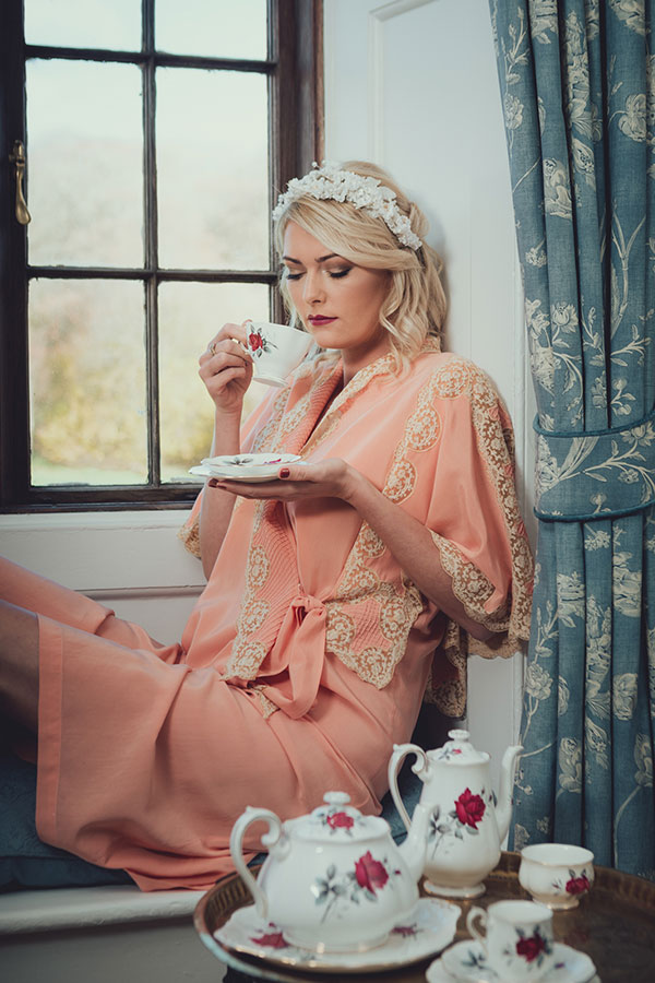 In the bedroom as the bride gets ready. The bride is wearing a peach coloured vintage dressing gown, looking out of the bedroom window and holding a dainty teacup.