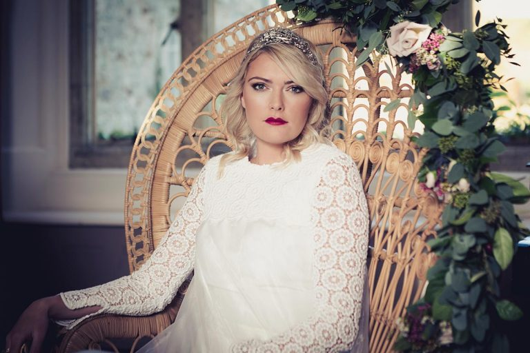 Warm, bohemian and ethereal. The bride reclines in a classical peacock chair at the dining table. The bride is wearing a glamorous head-dress and a classical cream coloured wedding dress sourced by Botanical Vintage. Autumnal light is streaming into the room behind her.