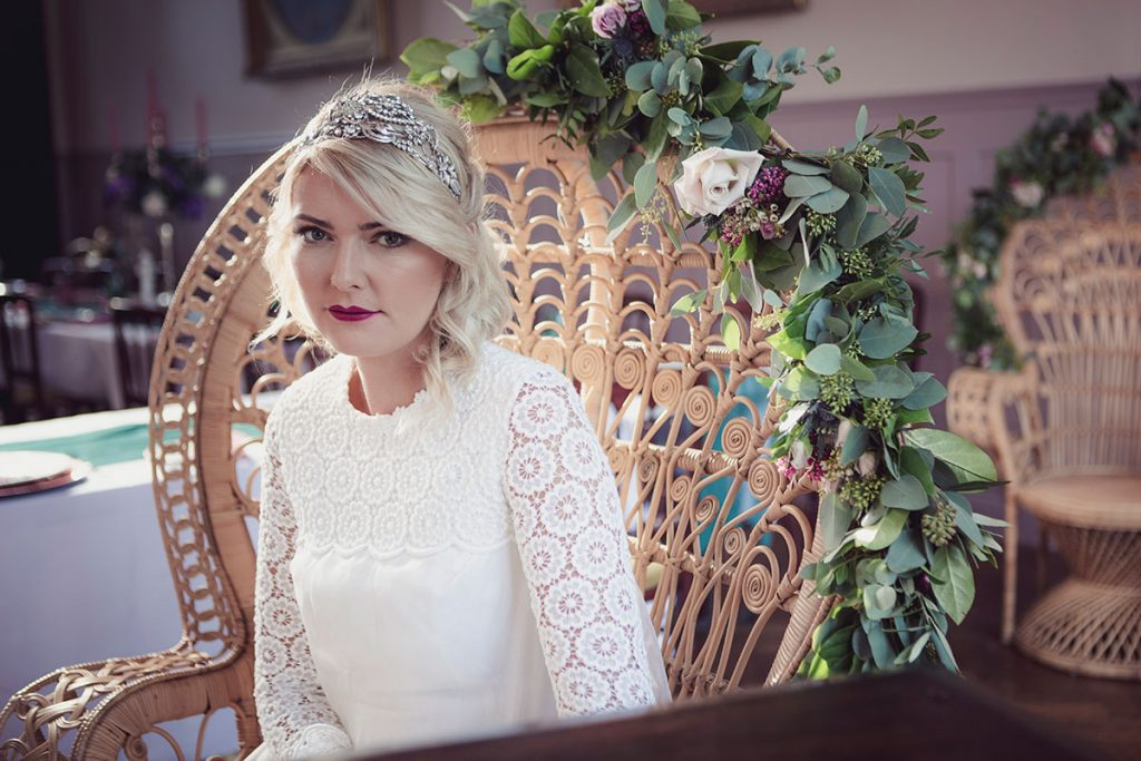 Reclining in a classical peacock chair at the dining table. The bride is wearing a glamorous head-dress and a classical cream coloured wedding dress sourced by Botanical Vintage. Autumnal light is streaming into the room behind her.