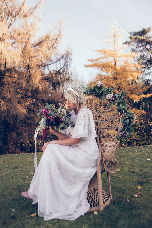 Sniffing the flowers. Our bride holds a beautiful bouquet of flowers, the bride stands in the grounds of the manor house wearing a vintage white wedding dress sourced by Botanical Vintage. The bride sits upon a stunning bridal peacock chair in the garden. The atmosphere is bohemian.