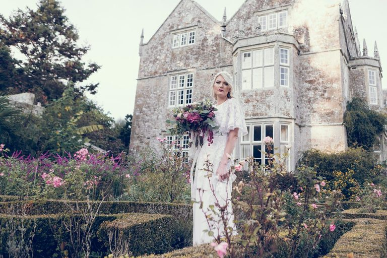Holding a beautiful bouquet of flowers, the bride stands in the grounds of the manor house wearing a vintage white wedding dress sourced by Botanical Vintage. The manor house is behind her, and she stands in amongst the flowers of a Victorian style country garden.
