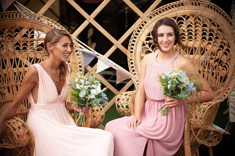 There are two bride maids holding a bouquet of flowers. They are sat in two peacock chairs supplied by Botanical Vintage