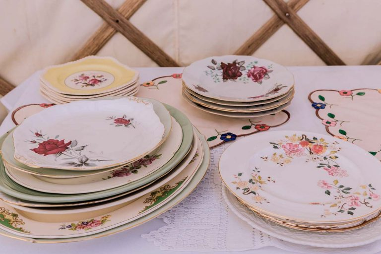 There are plates laid out on a table supplied by Botanical Vintage