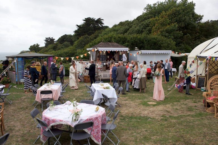 This is a photo of an outdoor wedding scene. The tables are laid out and the guests are mingling. The crockery has been supplied by Botanical Vintage