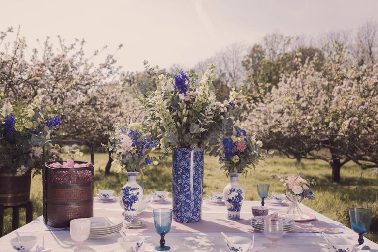 A laid table of vintage crockery soaked in a haze of golden sun