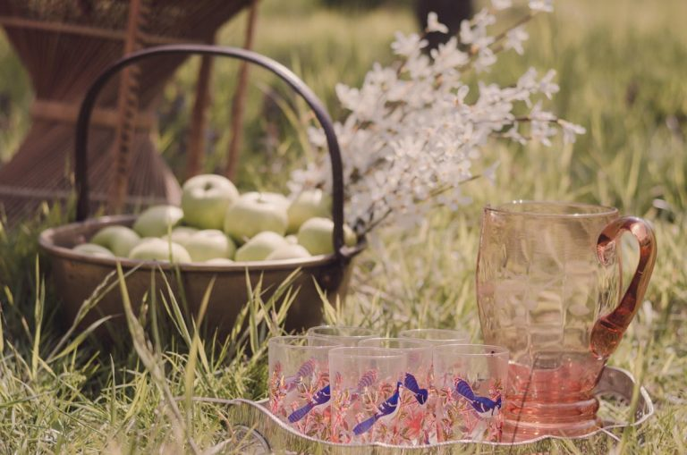 A basket full of fresh apples and a tray full of glass tumblers