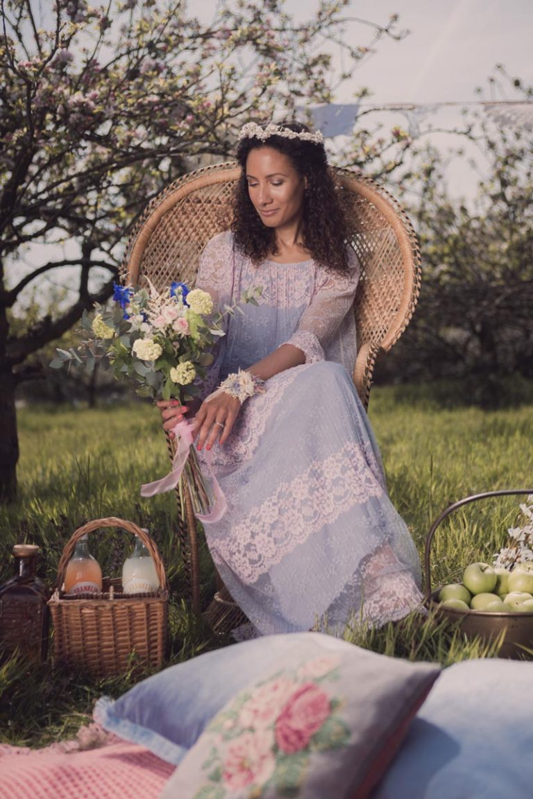 The bride sits upon a wicker peacock chair and looks at her bouquet