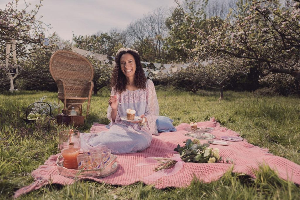 Our bride happily eats a cake whilst sat on the picnic blanket