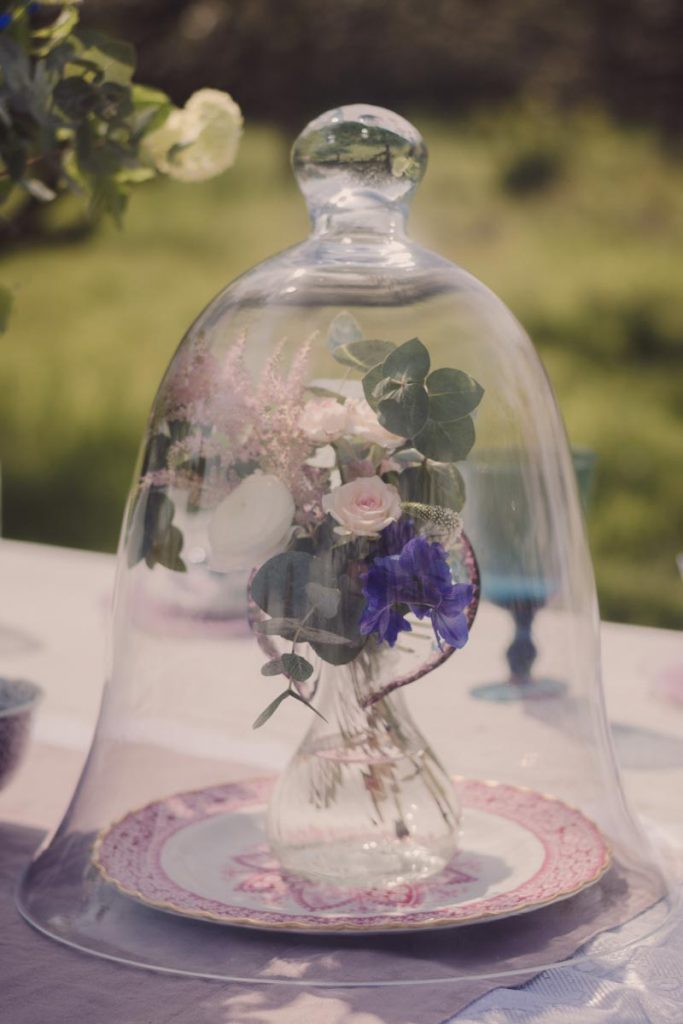 Bell shaped glass dome surrounds the flowers